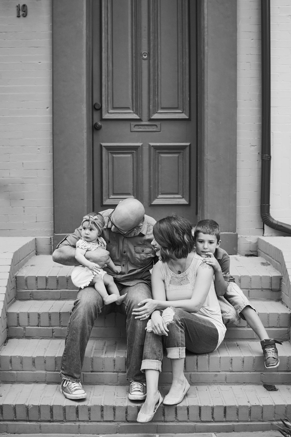 Family sits on their porch cuddled together for an intimate portrait in downtown RVA.