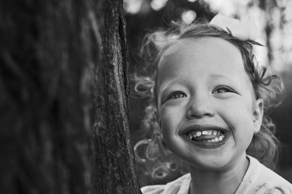 A bigg goofy grin of a happy girl during her family's portrait session by Richmond family photographer.