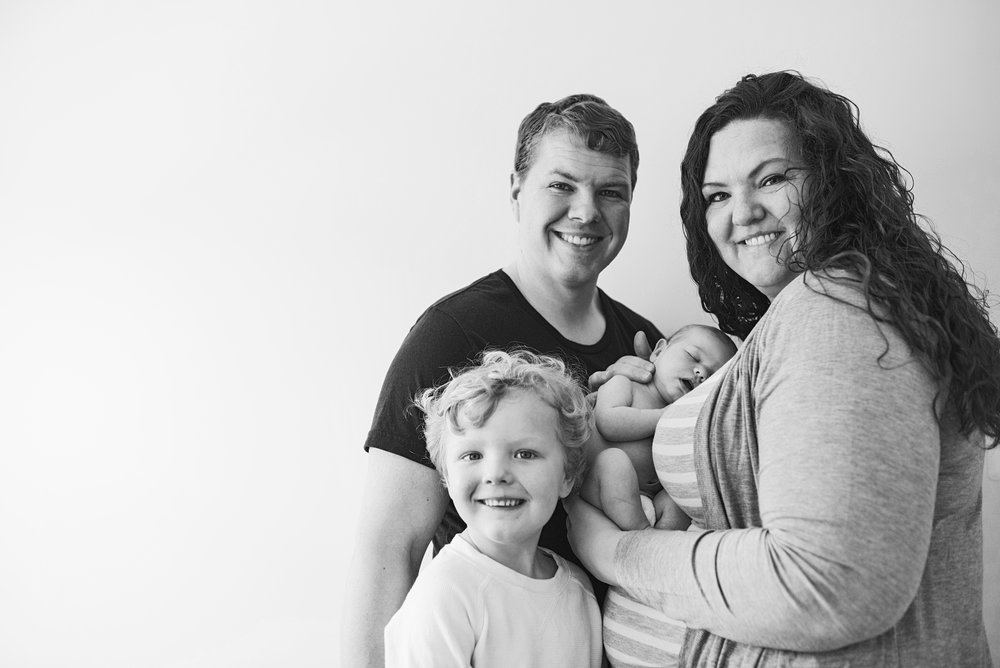 A simple white wall and beautiful family is all you need to take a stunning newborn family image at home or in a hospital!