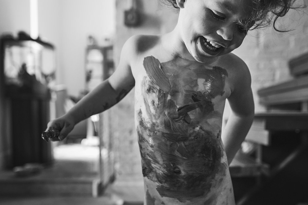 In home art session brings the paint to skin for this silly toddler in Jackson Ward, Richmond, Virginia.