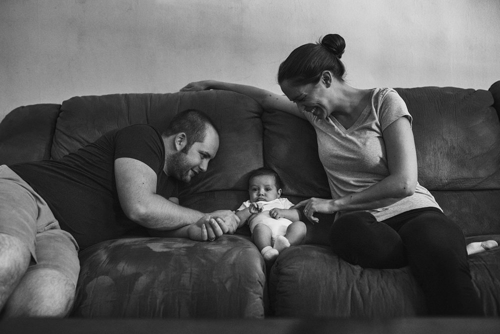 First time parents and their newborn sit and giggle on the couch during their family photo session in their new to them home, in downtown Manhattan, Kansas.