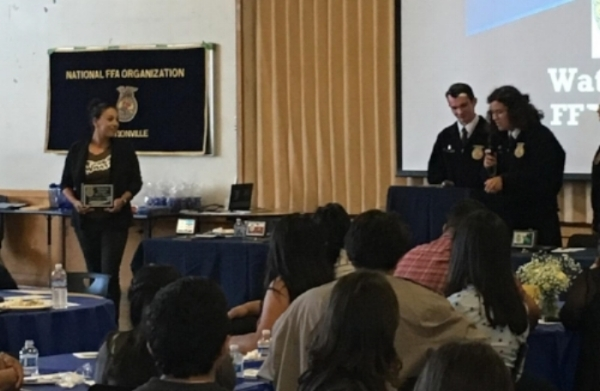 Programs Manager Irene Juarez O'Connell accepting an award on behalf of FoodWhat from the Watsonville Chapter of the Future Farmers of America at their awards banquet at Watsonville High School last month.