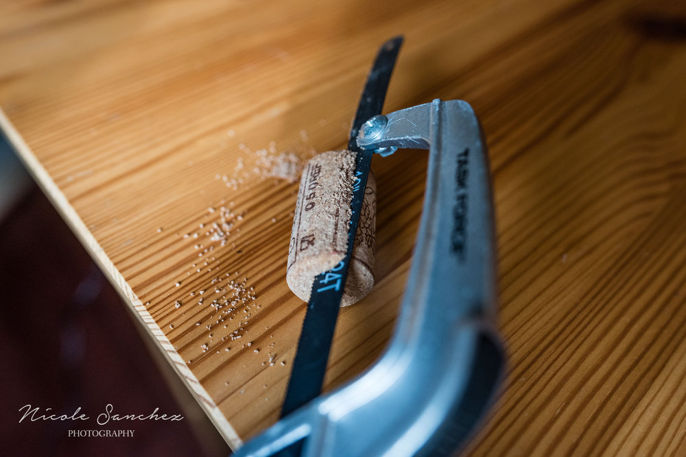 Using a hand saw to cut cork by Alexandria, VA Family Photographer Nicole Sanchez