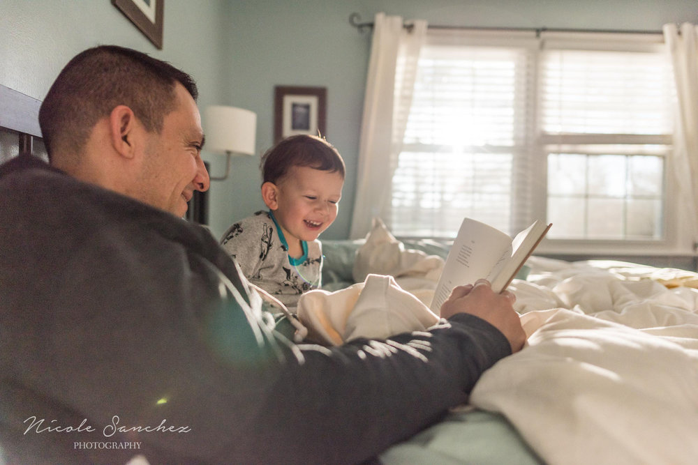 Father and son reading in bed by Alexandria, VA Family Photographer Nicole Sanchez
