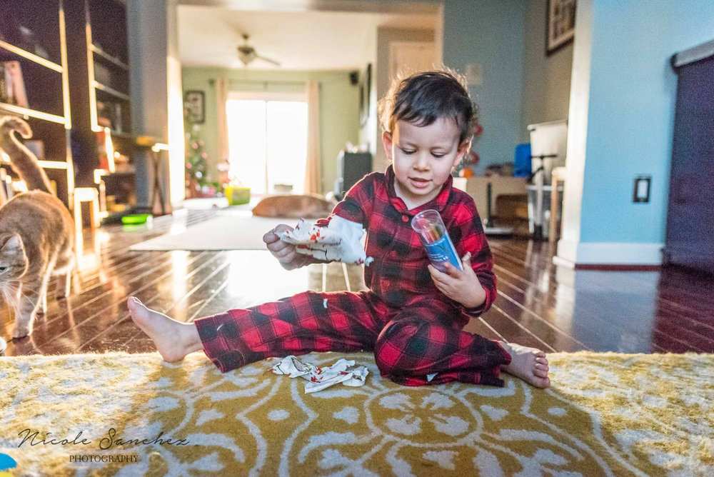 Boy opening present on Christmas morning by Alexandria, VA Lifestyle Family Photographer Nicole Sanchez
