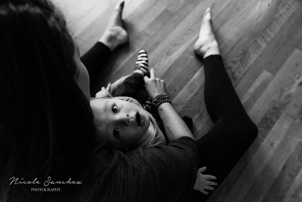 Boy looking up as mom puts on his shoes by Alexandria, VA Family Photographer Nicole Sanchez