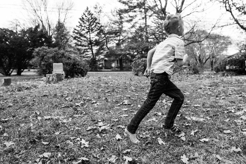 Boy chasing leaves outside by Northern Virginia Lifestyle Photographer Nicole Sanchez