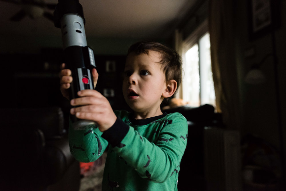 Boy-playing-with-lightsaber-in-pajamas-by-Northern-Virginia-Family-Photographer-Nicole-Sanchez