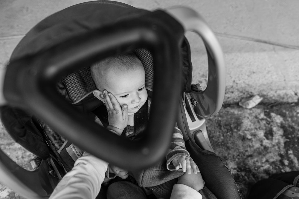 Boy touching his baby brother's cheek in car seat by Northern Virginia Family Photographer Nicole Sanchez