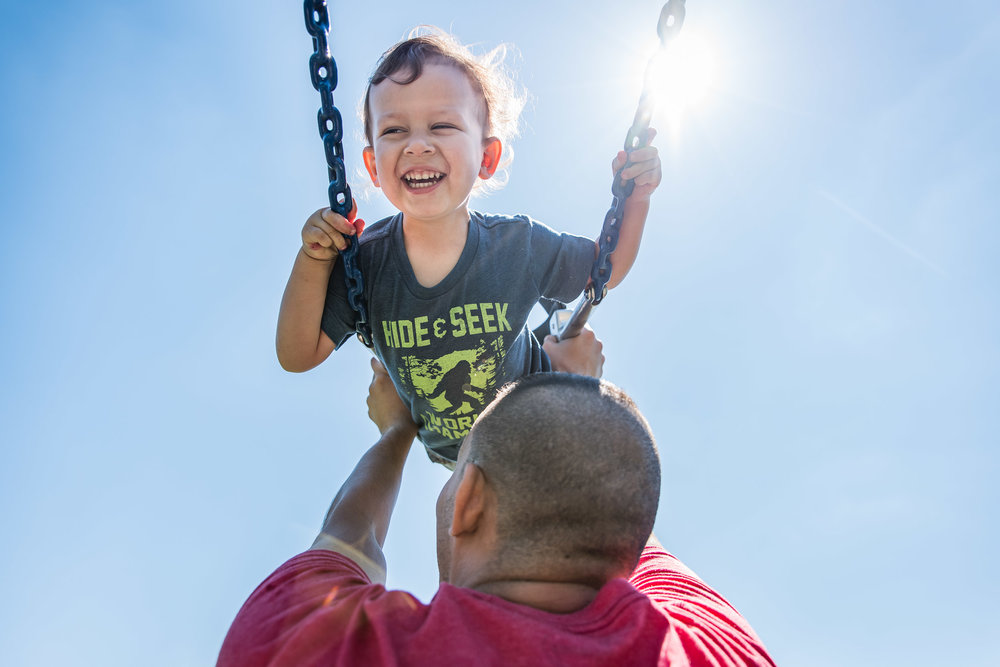 Boy on swings at Jones Point Park in Alexandria, Virginia by Family Photographer Nicole Sanchez
