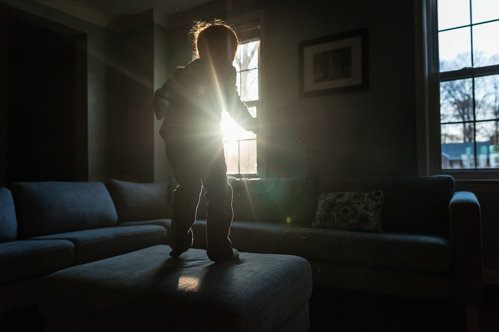 Boy jumping on ottoman with sun flare in Northern Virginia by Family Photographer Nicole Sanchez