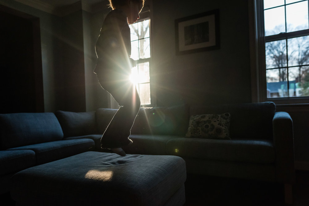 Boy jumping on couch with sun flare in Alexandria, VA by Family Photographer Nicole Sanchez