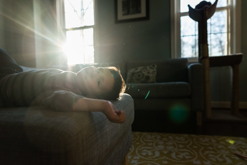 Boy resting on couch with sun flare by Northern Virginia Family Photographer Nicole Sanchez