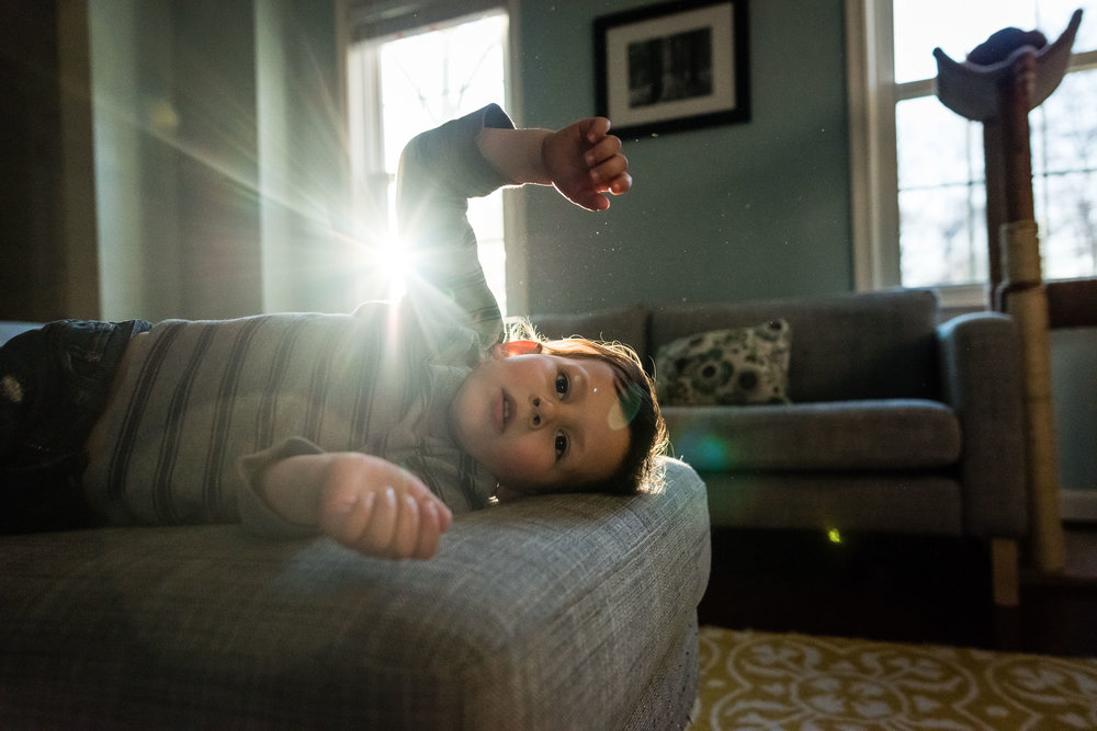 Boy resting on couch with Sun flare by Alexandria, VA Family Photographer Nicole Sanchez