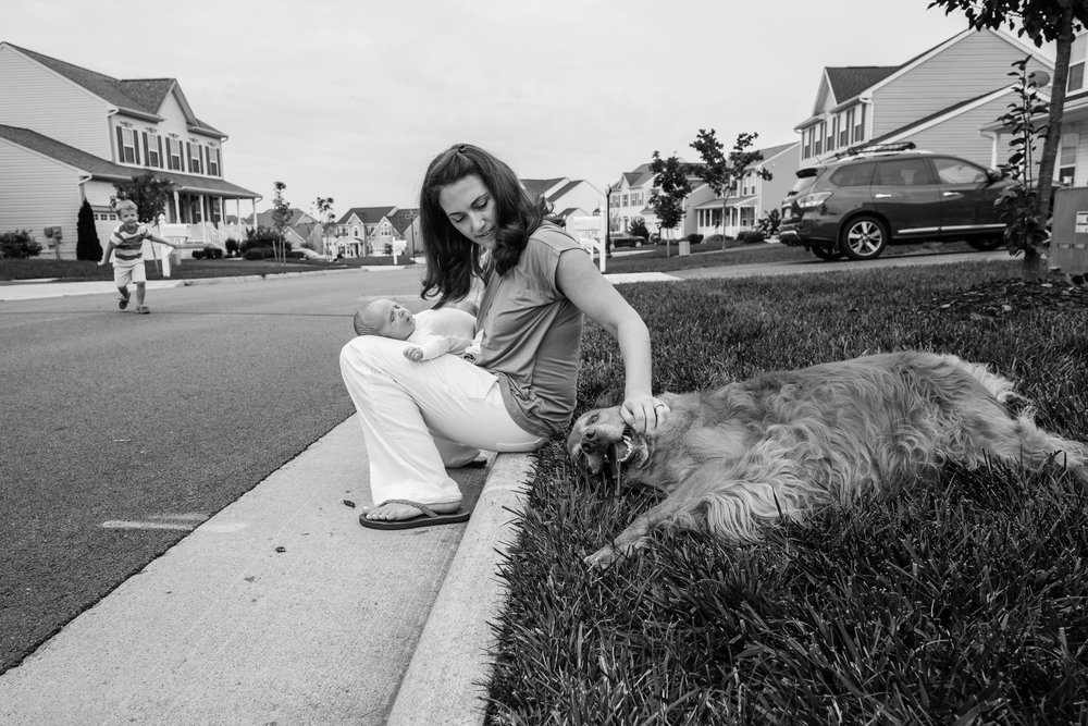 Mom holding newborn baby and petting dog in Northern Virginia neighborhood by Family Photographer Nicole Sanchez
