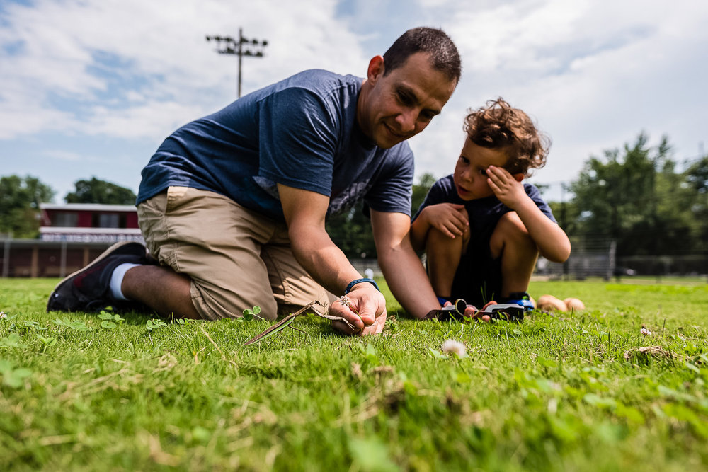 father and son examining large insect by northern virginia family photographer nicole sanchez
