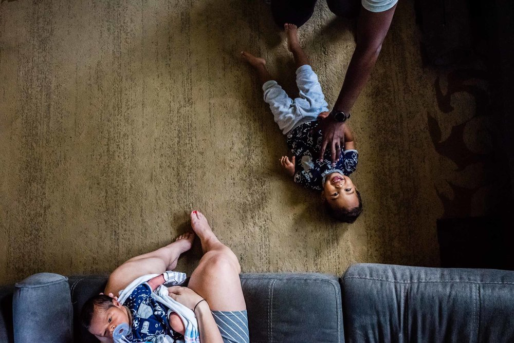 dad tickling toddler while mom watches with baby by family photographer nicole sanchez