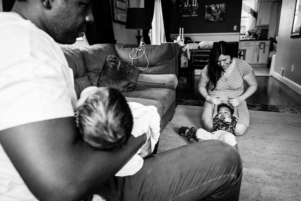 mom playing with older brother while dad holds baby by northern virginia family photographer nicole sanchez