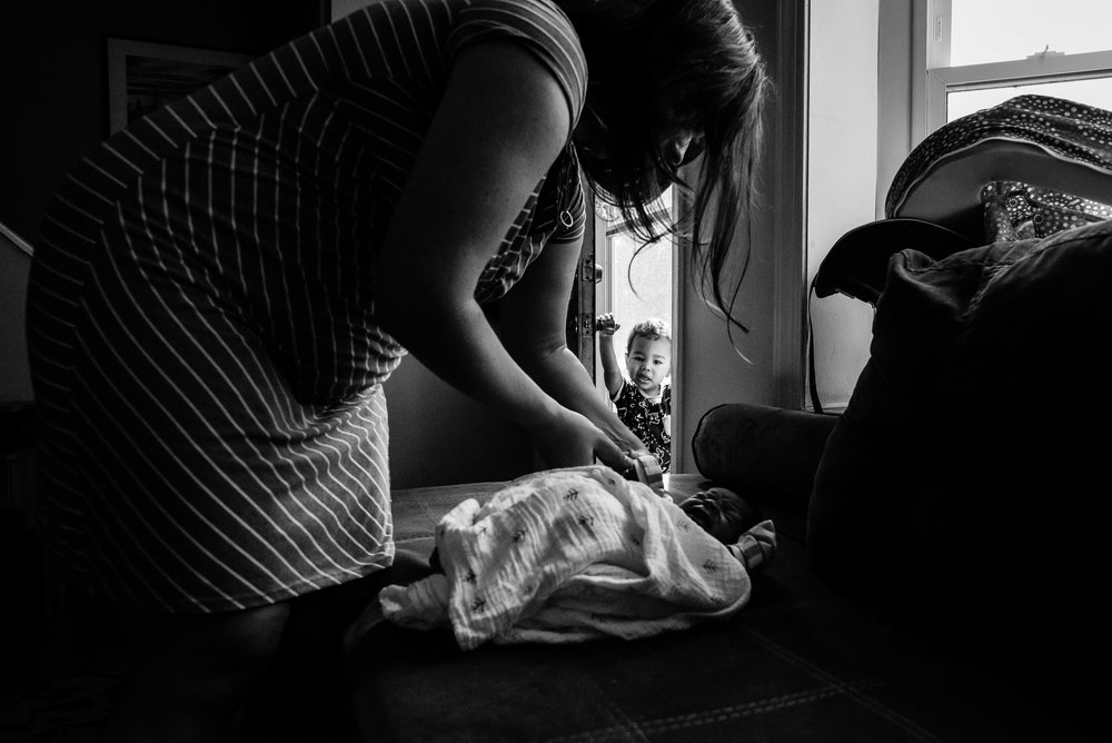 big brother watching mother swaddle baby brother by northern virginia family photographer nicole sanchez