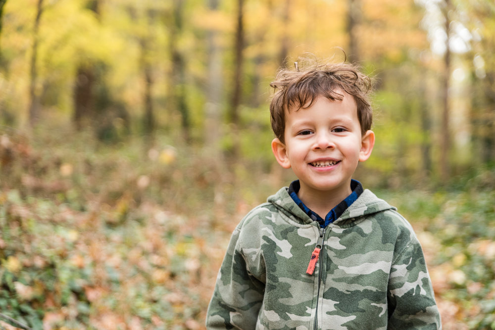 Boy smiling with fall leaves by Northern Virginia Family Photographer Nicole Sanchez