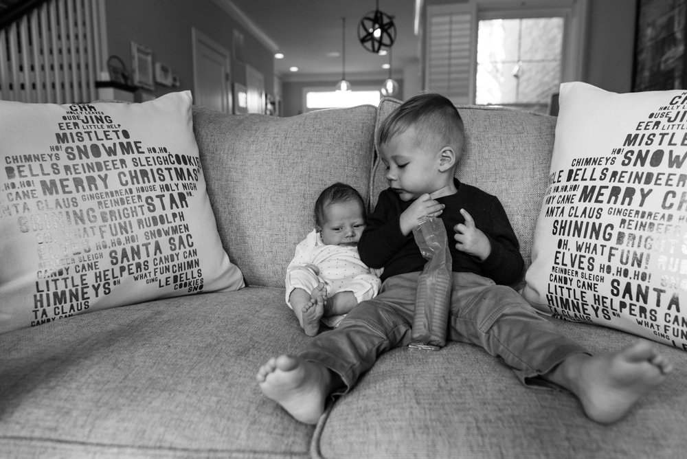 Boy looking at baby on couch while having a snack