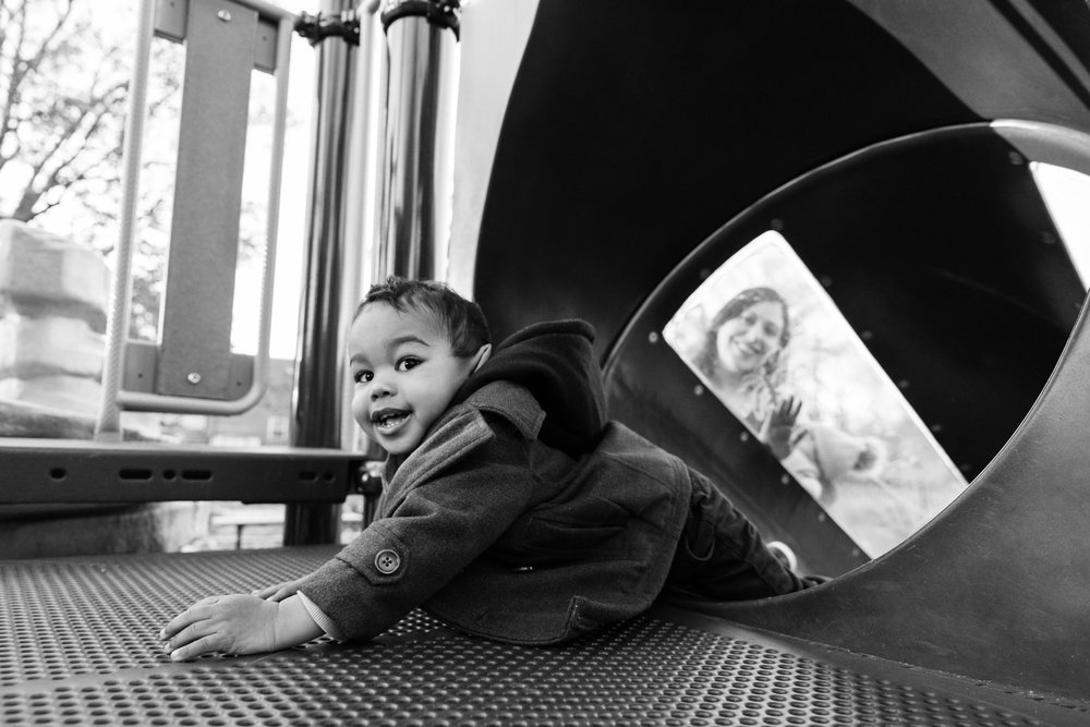 Toddler boy sliding backward down slide on playground
