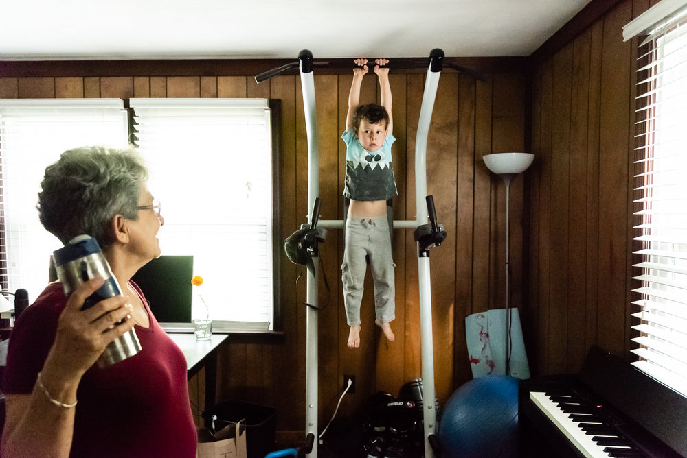 Boy hanging from pull-up bar by Northern Virginia Family Photographer Nicole Sanchez