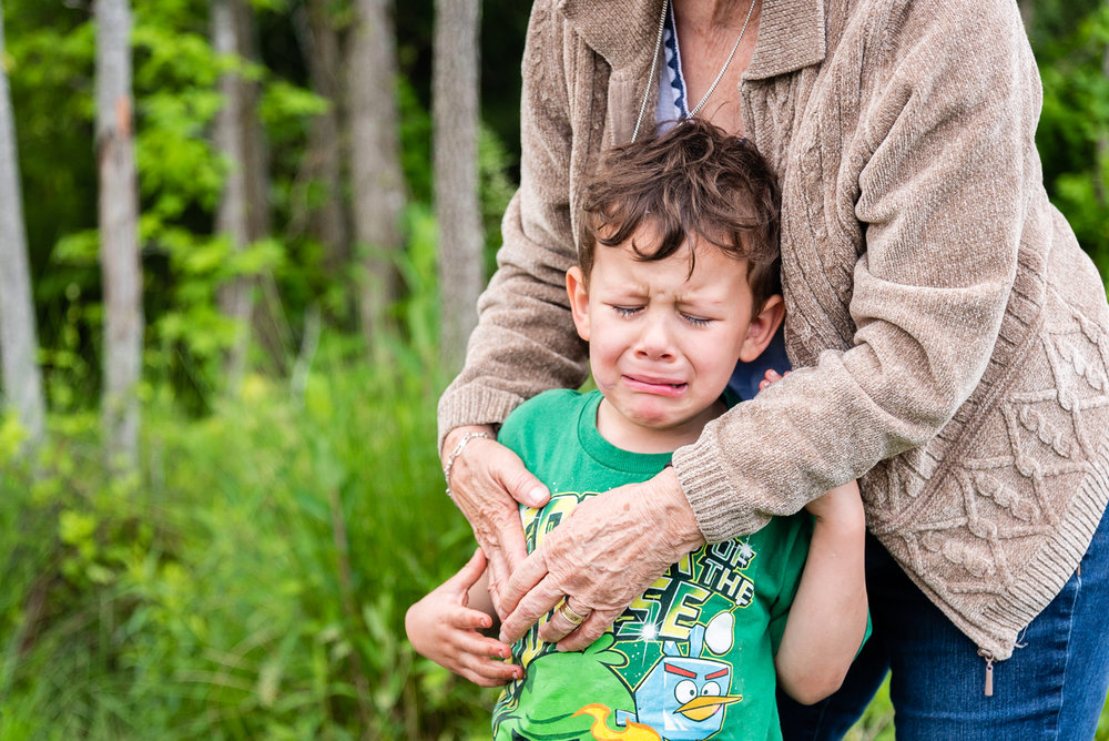 Crying boy being comforted by grandmother by Northern Virginia Family Photographer Nicole Sanchez