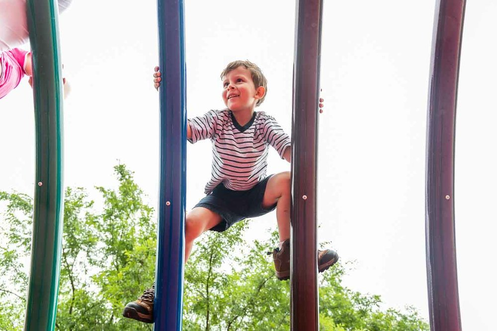 Boy climbing rainbow bars at Clemyjontri playground by Northern Virginia Family Photographer Nicole Sanchez