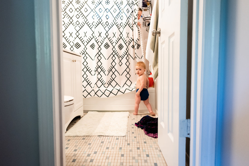 Toddler peeking in on mom in shower by Family Photographer Nicole Sanchez