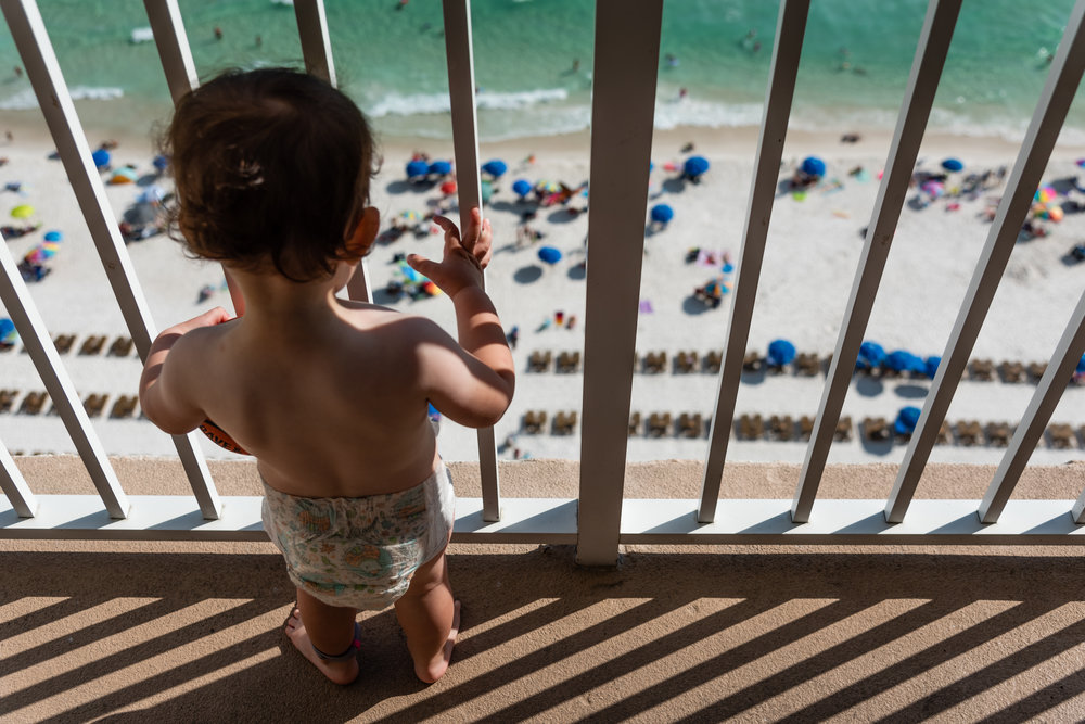 Toddler looking over balcony at beach by Northern Virginia Family Photographer Nicole Sanchez