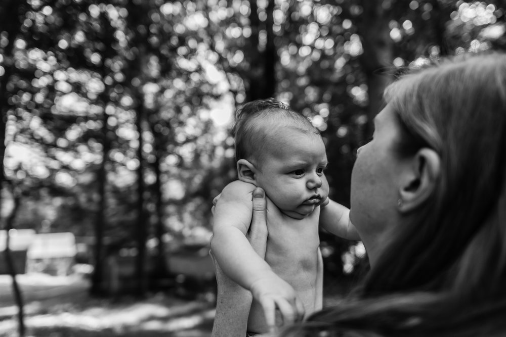 Mom holding new baby outside by Northern Virginia Newborn Photographer Nicole Sanchez