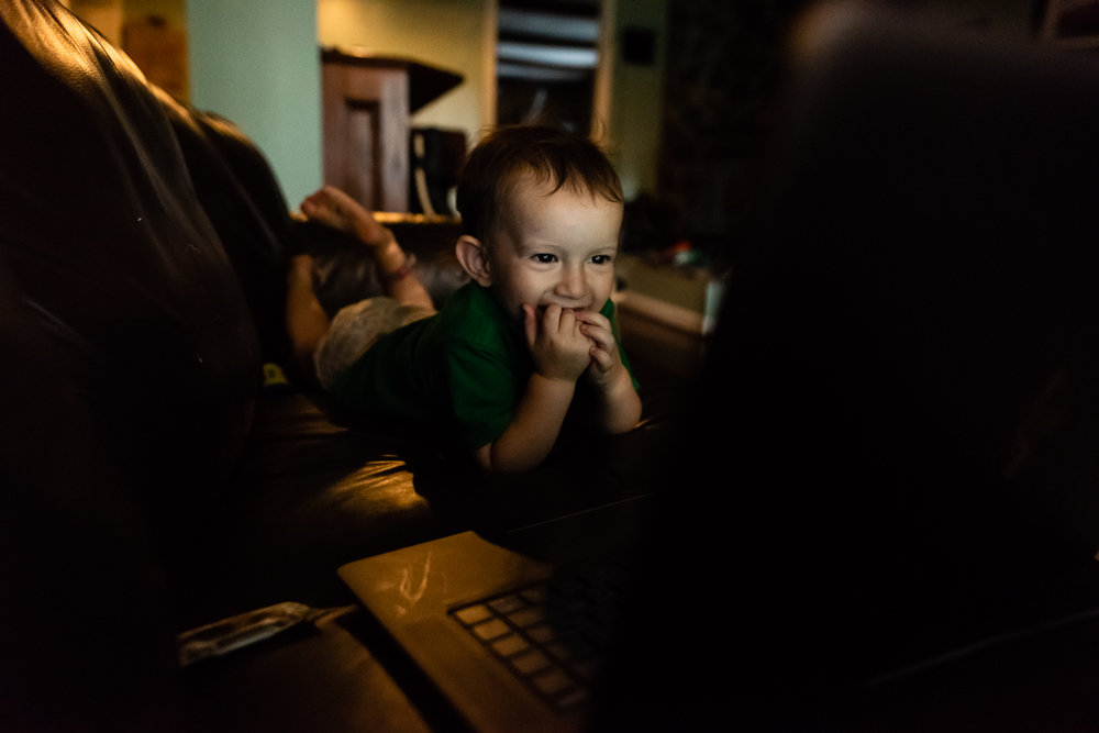 Toddler giggling while watching a family film by Northern Virginia Family Photographer Nicole Sanchez