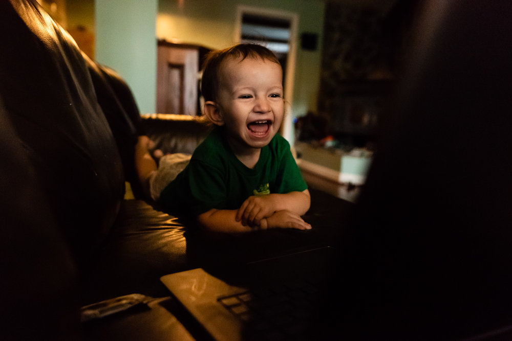 Baby laughing while watching his family film by Northern Virginia Family Photographer Nicole Sanchez