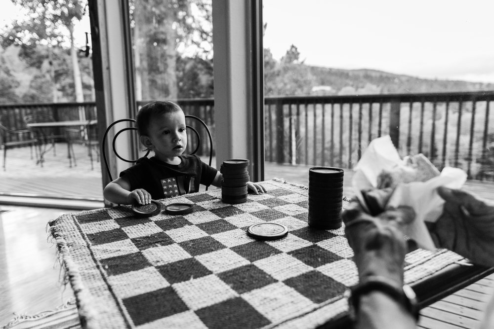 Toddler playing checkers with grandpa by Northern Virginia Family Photographer Nicole Sanchez
