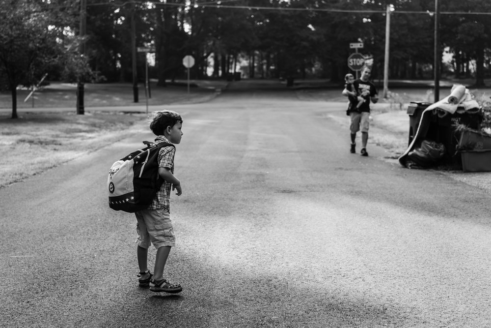 Boy with backpack waiting for dad and baby brother in Northern Virginia by Family Photographer Nicole Sanchez