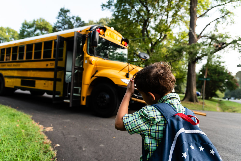Kindergartner anxiously waiting for school bus in Northern Virginia by Family Photographer Nicole Sanchez