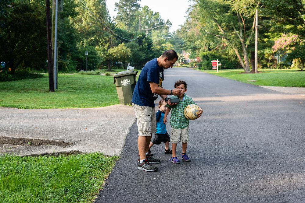 Dad feeding son while walking to school bus stop by Northern Virginia Family Photographer Nicole Sanchez