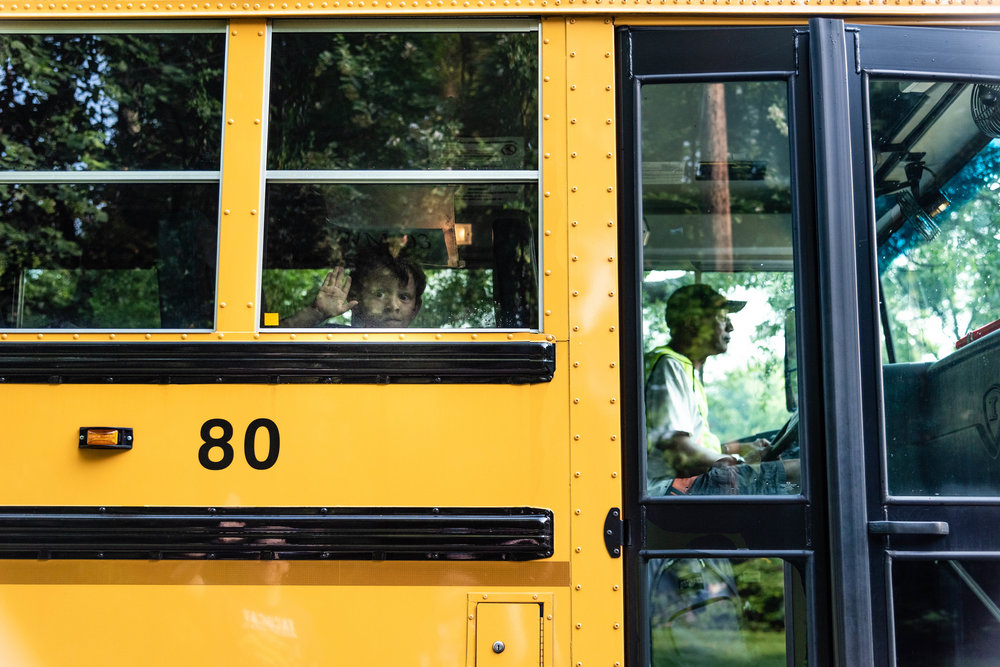 Kindergarten boy waving to family from school bus window in Northern Virginia by Family Photographer Nicole Sanchez