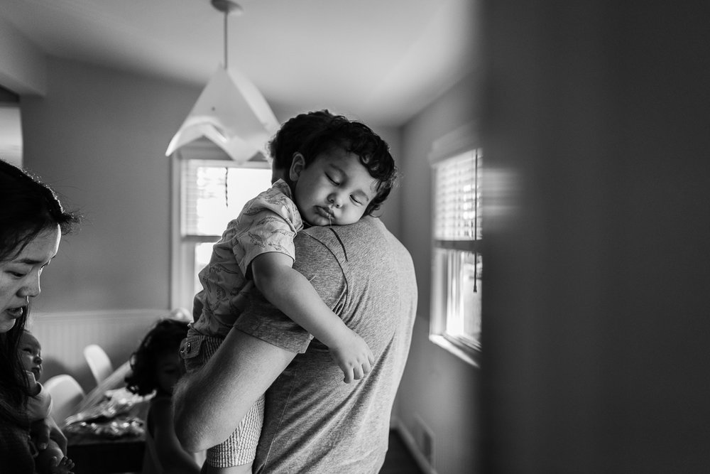 Toddler boy sleeping on Dad's shoulder while Mom takes shoes off by Northern Virginia Family Photographer Nicole Sanchez