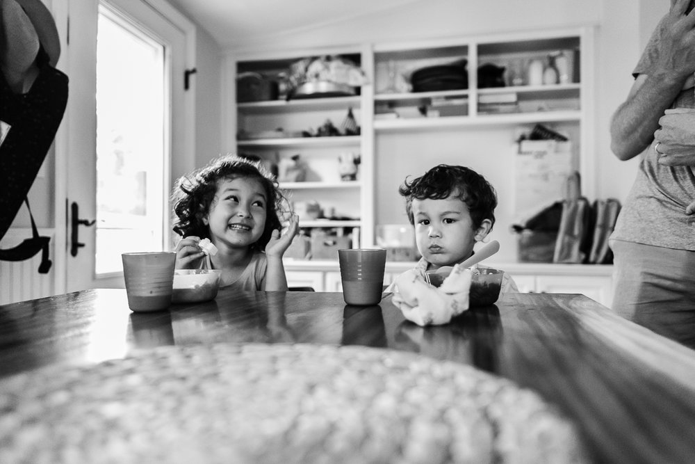 Brother and sister having a snack at kitchen table by Northern Virginia Family Photographer Nicole Sanchez