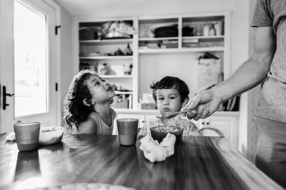 Father trying to feed toddler boy at kitchen table by Northern Virginia Family Photographer Nicole Sanchez