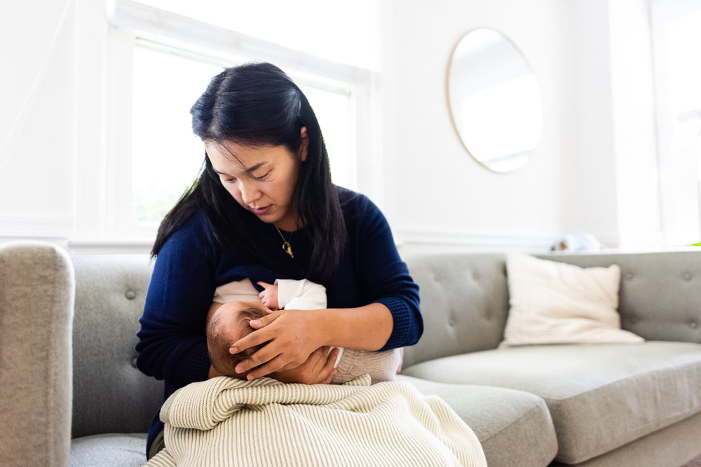 Mother nursing newborn on living room couch by Northern Virginia Family Photographer Nicole Sanchez