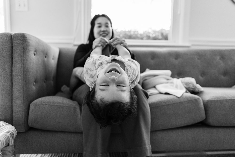 Toddler laughing upside down on mom's lap by Northern Virginia Family Photographer Nicole Sanchez