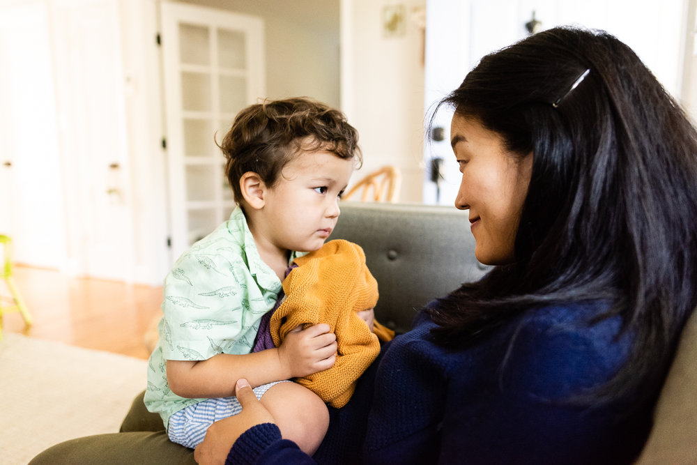 Toddler sitting in mom's lap on couch by Northern Virginia Family Photographer Nicole Sanchez