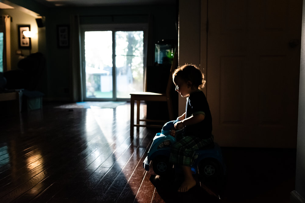 Boy riding car in house in early morning light by Family Photographer Nicole Sanchez