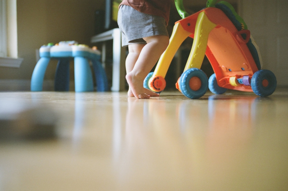 Toddler walking with a walker on wood floors, Austin family photographer