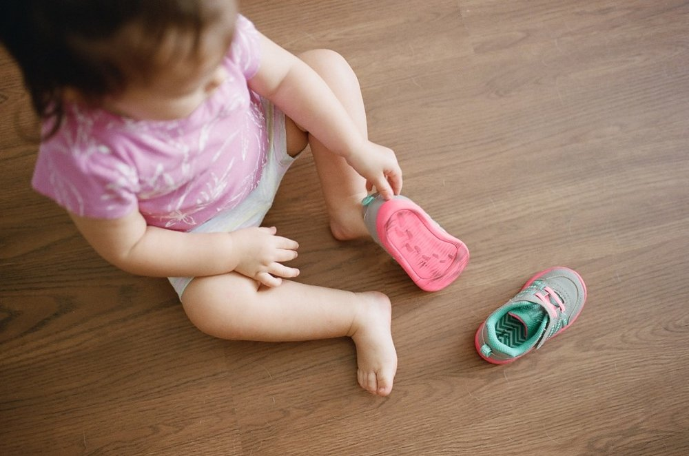 toddler trying to put her own shoes on