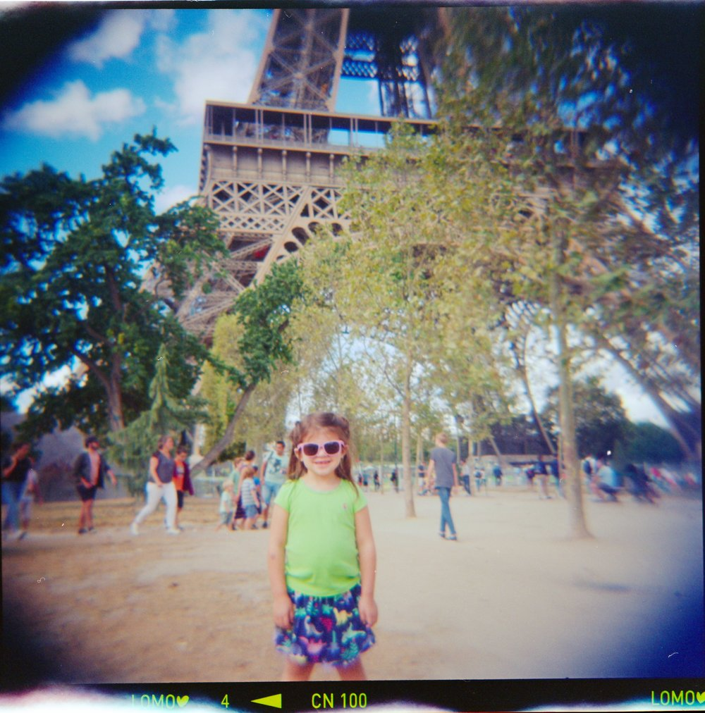 toddler standing in front of the Eiffel Tower