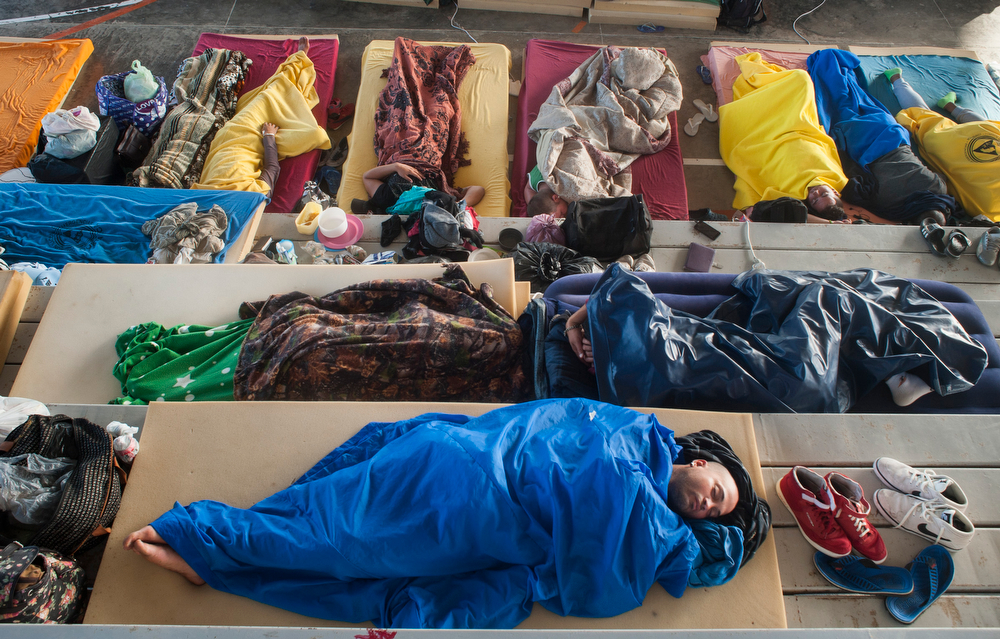 Alejandro Estebán Galvez, 23, sleeps on bleachers of a high school gymnasium among other Cuban migrants on the morning of Dec. 29, 2015 in La Cruz, Costa Rica. The public schools, churches and community buildings in La Cruz were converted into temporary shelters to house the several thousand migrants.